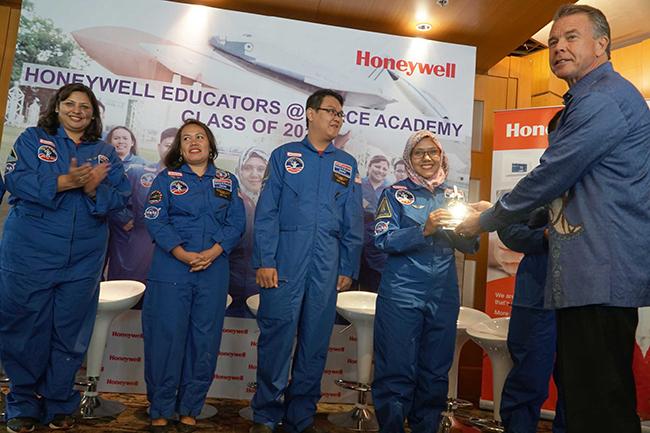 Presdir PT Honeywell Indonesia, Alex Pollack (kanan) menyerahkan replika pesawat luar angkasa saat jumpa pers dan penyambutan 7 guru yang telah selesai mengikuti program pelatihan intensif khusus dama bidang STEM di Akademi Luar Angkasa di AS, Rabu (4/10). Para guru yang ikut serta dalam program selama 5 hari ini mengikuti pelatihan intensif berfokus pada Sains dan eksplorasi luar angkasa serta latihan latihan yang digunakan para astronot, seperti simulasi jet dan misi antariksa, latihan kemahiran di darat dan air, dan program dinamika penerbangan interaktif,tujuannya adalah untuk membekali para guru teknik pengajaran yang inovatif hingga dapat membuat suasana belajar sains dan matematika di kelas menjadi lebih hidup dan menginspirasi para murid dalam mata pelajaran.