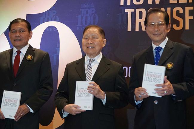 """Presiden Direktur PT Bank Central Asia Tbk (BCA) Jahja Setiaatmadja ( kanan) menerima buku """"No Nonsense Leadership"""" karya Robby Djohan yang diserahkan secara langsung oleh Putri Robby Djohan - Wita Djohan (kedua kanan) hadir pula  Senior Banker sekaligus Pendiri Lippo Group Mochtar Riady (tengah), CEO Citibank Indonesia Batara Sianturi ( kiri) pada acara Peluncuran Buku Top 100 Bankers di Jakarta, Selasa (28/11)."""